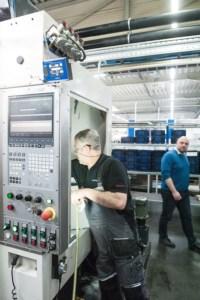Ein Produktionsmitarbeiter beim Säubern der Fräsmaschine, in die das Inline-Messsystem ATC eingebaut ist. Oben links das blaue Kästchen ist das GUI des ATC